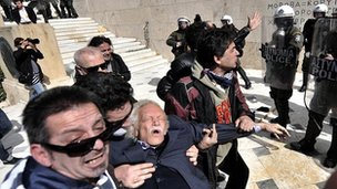 Manolis Glezos is assisted by protesters outside the Greek parliament in Athens in March 2010