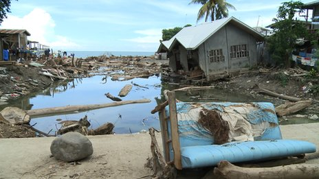 Logs, debris and a damaged house in Iligan