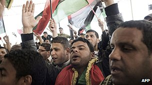 Libyan men mark the first anniversary of the uprising which overthrew Gaddafi