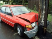 Red car smashed against telegraph pole
