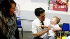 Ed Miliband with 16-month-old Marley Richardson and his mother Carla Toner during a visit to Royal Bolton Hospital