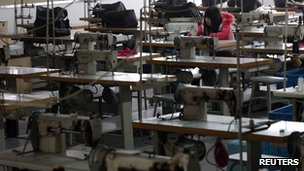 A worker works while surrounded by unmanned sewing machines at the production line of a bag factory in Yiwu, Zhejiang province (file photo)