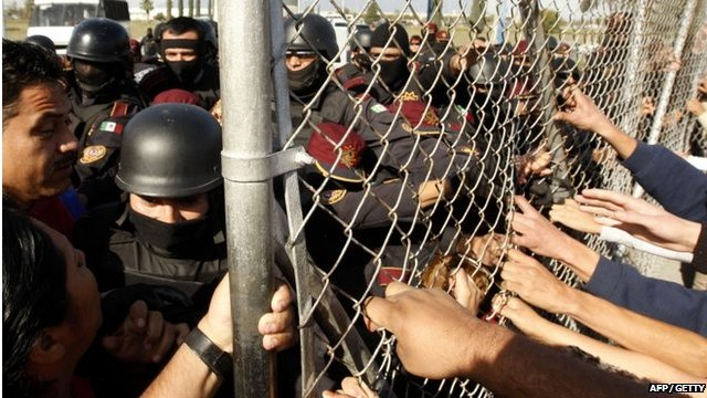 Relatives of inmates tug at the fence at Apodaca prison