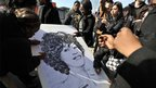 Fans sign a large poster while they gather on the streets near the New Hope Baptist Church as a private funeral for singer Whitney Houston is held at the church on February 18, 2012 in Newark, New Jersey.