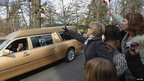Fans throw flowers at the hearse on the way to the cemetery, 19 Feb 12