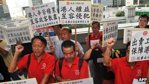 Protesters hold banners against the ruling allowing domestic workers to apply for residency 