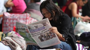 A domestic worker reading a newspaper