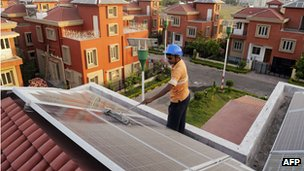 Worker installing solar panels on roof of house