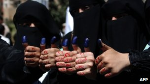 Yemeni women show their ink-stained thumbs as their hands read 'February 21, a new Yemen' to show their support for next week's presidential election