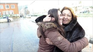 Spaniard Patricia Cigala says goodbye to her visiting mother at a bus stop in Munich