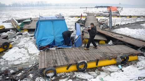 People try to salvage boats among ice on River Danube in Zemun near Belgrade