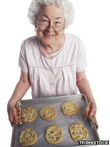 An elderly lady with a tray of biscuits