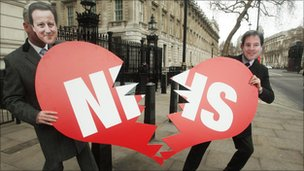 Protesters holding NHS sign