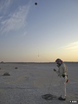 Researcher Nathan Craig operating the kite camera at the ancient trackway site in the United Arab Emirates