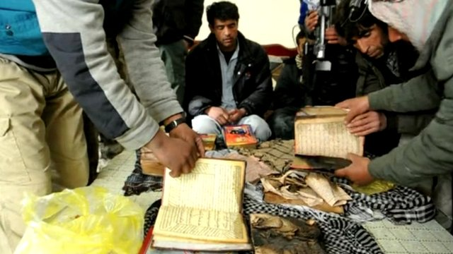 Charred books, alleged to be the Koran, are examined