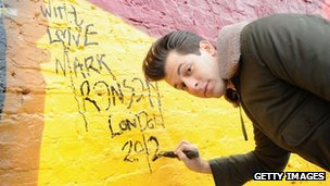 "Mark Ronson signing the ""Beat Wall"" near the Olympic Stadium in London"