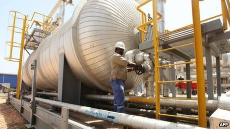An oil worker turns a spigot at an oil processing facility in Palouge oil field in Upper Nile state