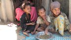 Faduma Aden Mohamud's children eating outside their house in a displacement camp in Mogadishu, the capital of Somalia