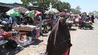 Faduma Aden Mohamud walking along a street near market stall in the Somali capital, Mogadishu