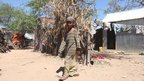 Faduma Aden Mohamud's daughter walks past houses in the displacement camp in Hodan district of the Somali capital