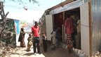 People outside Faduma Aden Mohamud's small shop in a camp for people displaced in the Somali capital, Mogadishu