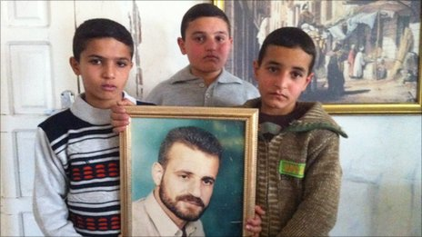 The three al-Haddar brothers hold up a portrait of their father