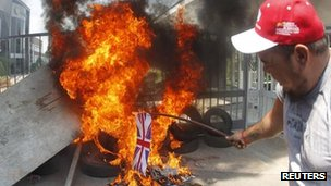 A left-wing activist sets fire on a British flag during a demonstration outside British drugmaker GlaxoSmithKline Laboratories in Buenos Aires February 16
