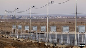 A picture shows water tanks at a partially set up camp in Mafraq city, near Jordan's northern border with Syria