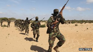 Members of Somalia&#039;s al-Shabab militant group parade during a demonstration to announce their integration with al-Qaeda south of the capital, Mogadishu, on 13 February 2012