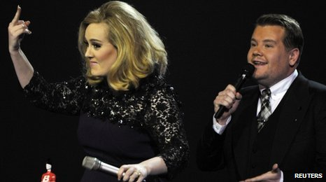 Adele and James Corden on stage at the Brit awards.