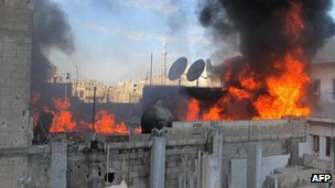 A handout picture released by activist group the Local Co-ordination Committees in Syria (LCC Syria) on 22 February 2012 shows fire on the roof of a building in the Baba Amr neighbourhood of the flashpoint city of Homs, allegedly during the bombardment of the city