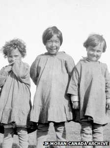 Two mixed-race children stand either side of an Inuit