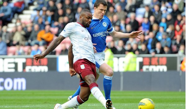 Darren Bent shoots under pressure from Gary Caldwell
