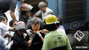 Rescue workers pull driver Marcos Cordoba from the train