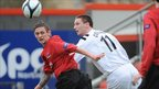 Matthew Snoddy of Crusaders competes against Lisburn Distillery's Mark Cooling