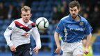 Rory Carson of Ballymena United goes for the ball with Glenavon opponent Mark Turkington