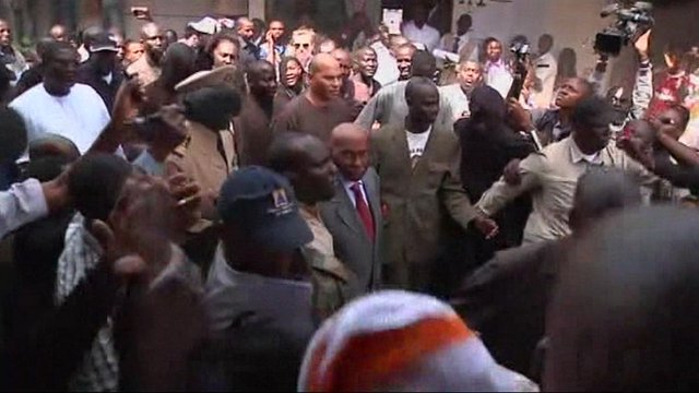 Mr Wade (centre) is ushered through a crowd