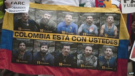 A man holds a banner with pictures of the ten Colombian police and military officers still held captive as hostages of the Farc in a demonstration in December 2011
