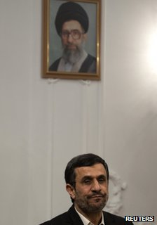 Mahmoud Ahmadinejad sits in front of a portrait of Ayatollah ali Khamenei