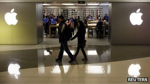 A couple walks past an Apple store in Shanghai
