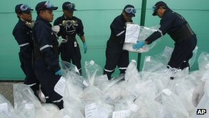 City employees organize seized bags of cocaine to be burned at a police base in Lima, Peru, 7 February 2012.
