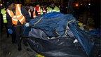 A bailiff removes a tent