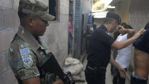 Soldier stands guard as police look for drugs and weapons in San Salvador, El Salvador&#039;s capital in January 2012