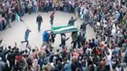 Hundreds of people ring an open coffin, held up by a group of men waving an old Syrian flag used by opposition groups (27 February 2012)
