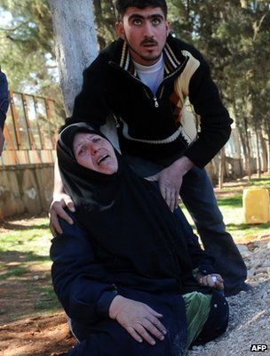 A woman is comforted at a funeral in Idlib, 25 February 2012