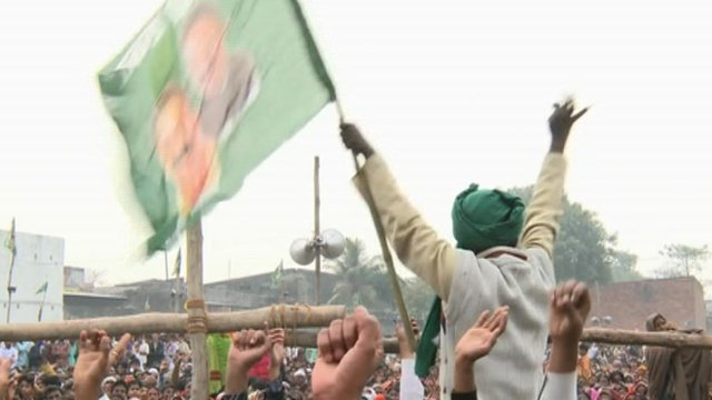 Man waving flag featuring the face of Mukhtar Ansari, a candidate for election who is in jail facing charges including murder