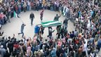 Hundreds of people ring an open coffin, held up by a group of men (27 February 2012)