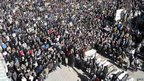 Large crowd surrounds a line of coffins, Homs (26 February 2012) 