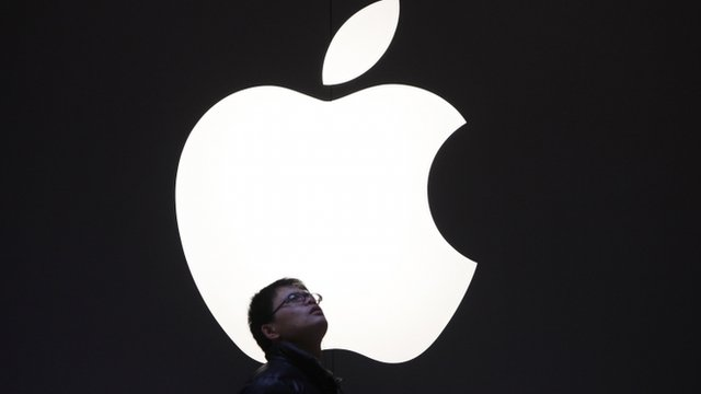 Man standing underneath Apple logo