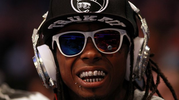 Hip-hop artist Lil' Wayne wearing diamond studded beats headphones
